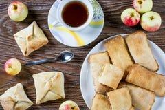 Οι πίτες λίγων μήλων ή οι κύκλοι εργασιών μήλων με την κανέλα σε ένα άσπρο πιάτο με το τσάι κοιλαίνουν και ώριμα μήλα στο υπόβαθρ Στοκ Εικόνες