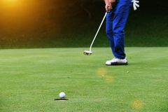Οι παίκτες γκολφ βάζουν το γκολφ στο γήπεδο του γκολφ βραδιού στην Ταϊλάνδη στοκ εικόνες
