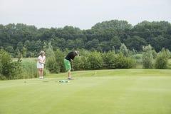 Οι παίκτες γκολφ παίζουν τη σφαίρα στο πράσινο Στοκ Φωτογραφία