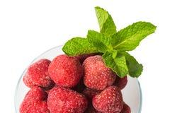 Οι παγωμένες φράουλες και ένα κλαδάκι της φρέσκιας μέντας, τοπ άποψη, απομονώνουν Στοκ Εικόνες