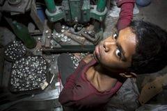 Οι παιδικές εργασίες λειτουργούν τη σφαίρα χάλυβα κάνοντας το εργοστάσιο Στοκ Εικόνες