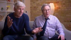 Οι παλαιοί αρσενικοί φίλοι που κάθονται μαζί στον καναπέ που προσέχει τη TV παίρνουν εξαιρετικά διασκεδασμένοι και συγκλονισμένοι απόθεμα βίντεο