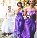 Οι παράνυμφοι βοηθούν τη νύφη για να βάλουν στα σκουλαρίκια και το περιδέραιο στοκ εικόνα με δικαίωμα ελεύθερης χρήσης