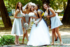 Οι παράνυμφοι κλίνουν στη νύφη ενώ θέτουν στο πάρκο Στοκ Φωτογραφίες