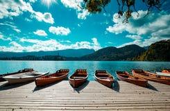 Οι παραδοσιακές ξύλινες βάρκες Pletna στο backgorund της εκκλησίας στο νησί στη λίμνη αιμορράγησαν, Σλοβενία Ευρώπη στοκ φωτογραφία