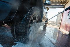 Οι παφλασμοί του νερού με το σαπούνι πετούν στις διαφορετικές κατευθύνσεις από ρεύμα μιας υψηλής πίεσης Το άτομο πλένει το πλύσιμ στοκ εικόνες με δικαίωμα ελεύθερης χρήσης