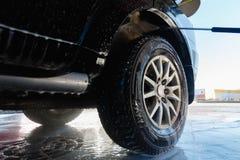Οι παφλασμοί του νερού με το σαπούνι πετούν στις διαφορετικές κατευθύνσεις από ρεύμα μιας υψηλής πίεσης Το άτομο πλένει το πλύσιμ στοκ φωτογραφία