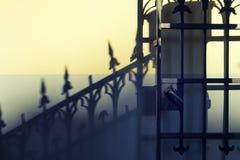 Οι παλαιές πύλες επεξεργασμένος-σιδήρου με μια σκιά στον τοίχο στοκ φωτογραφίες