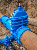 Οι παλαιοί μεγάλοι υδροσωλήνες ποτών ένωσαν με τις νέες μπλε βαλβίδες και τα νέα μπλε κοινά μέλη Τελειωμένη επισκευασμένη διοχέτε Στοκ εικόνες με δικαίωμα ελεύθερης χρήσης