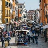 Οι πεζοί περπατούν εκτός από την οργάνωση στάβλων αγοράς στην περιοχή Cannaregio της Βενετίας Στοκ Εικόνα
