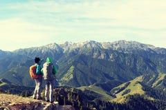 Οι πεζοποριεις φίλοι απολαμβάνουν τη θέα σχετικά με το βουνό Στοκ φωτογραφία με δικαίωμα ελεύθερης χρήσης