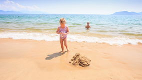 Οι περίπατοι μικρών κοριτσιών από τη θάλασσα χύνουν το νερό στην άμμο Castle στην παραλία απόθεμα βίντεο