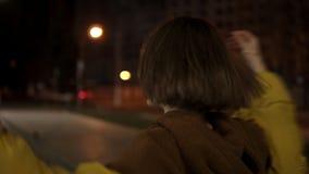 Οι περιστροφές νέων κοριτσιών στο θάρρος, ρίχνουν ένα κίτρινο σακάκι πέρα από το κεφάλι της, έχουν τη διασκέδαση άλμα απόθεμα βίντεο