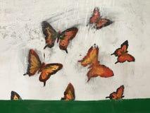Οι πεταλούδες σε έναν τοίχο είναι πορτοκαλιές και πετούν πέρα από έναν πράσινο φράκτη Στοκ φωτογραφία με δικαίωμα ελεύθερης χρήσης