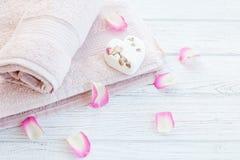 Οι πετσέτες και το άλας λουτρών και αυξήθηκαν πέταλα Υπόβαθρο Η έννοια Στοκ Εικόνες