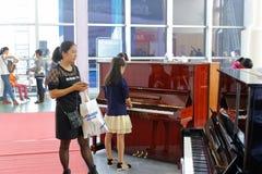 Οι πελάτες επιλέγουν το πιάνο στα μουσικά όργανα Στοκ εικόνες με δικαίωμα ελεύθερης χρήσης