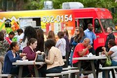 Οι πελάτες κάθονται και τρώνε το μεσημεριανό γεύμα που αγοράζεται από τα φορτηγά τροφίμων της Ατλάντας Στοκ φωτογραφίες με δικαίωμα ελεύθερης χρήσης