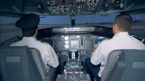 Οι πιλότοι παίρνουν το αεροπλάνο μακριά σε έναν προσομοιωτή πτήσης 4K απόθεμα βίντεο