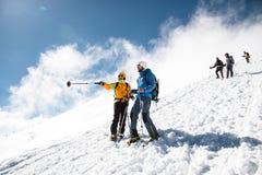 Οι πλήρως εξοπλισμένοι επαγγελματικοί ορειβάτες κατεβαίνουν κάτω από τη χιονώδη κλίση στον ηλιόλουστο καιρό Στοκ Φωτογραφία