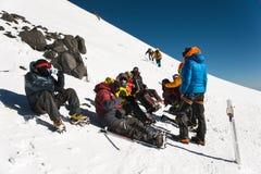 Οι πλήρως εξοπλισμένοι επαγγελματικοί ορεσίβιοι σε μια στάση κάθονται σε μια χιονώδη κλίση στον ηλιόλουστο καιρό στοκ φωτογραφία
