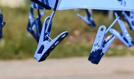 Οι πλαστικοί συνδετήρες υφασμάτων κρεμούν στη γραμμή ενδυμάτων Στοκ Φωτογραφία