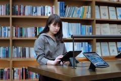 Οι πληροφορίες αναζήτησης κοριτσιών στη βιβλιοθήκη Στοκ Φωτογραφίες