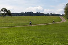 οι ποδηλάτες σε μια απόσταση βλέπουν σε ένα καλοκαίρι ηλιόλουστη ημέρα στοκ εικόνα