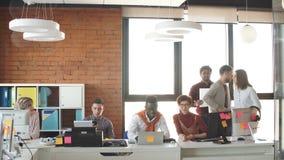 Οι πολυεθνικοί νέοι εργαζόμενοι γραφείων στα περιστασιακά ενδύματα συνεργάζονται μαζί στο εσωτερικό απόθεμα βίντεο