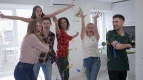 Οι πολυφυλετικοί φίλοι που παίζουν με το κομφετί στους σε αργή κίνηση, ευτυχείς νεαρούς άνδρες και τις γυναίκες χορεύουν και έχου