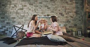 Οι πολυ εθνικές κυρίες έχουν το χρόνο πιτσών στο κόμμα sleepover στο κρεβάτι ευτυχές αυτοί που τρώνε και που αισθάνονται ευτυχείς απόθεμα βίντεο