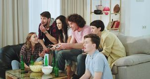 Οι πολύ εντυπωσιασμένοι και συγκεντρωμένοι φίλοι έχουν έναν χρόνο διασκέδασης μαζί στο καθιστικό δύο τους που παίζουν σε ένα τηλε απόθεμα βίντεο