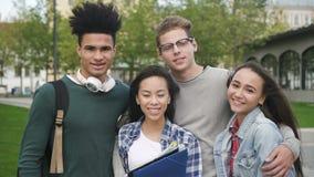 Οι πολύ συμπαθητικοί και φιλικοί σπουδαστές αναμιγνύω-φυλών στέκονται μαζί κοντά στο κολλέγιο απόθεμα βίντεο