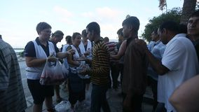 Οι πολεμικοί πρόσφυγες στέκονται σε μια σειρά αναμονής να λάβουν τη ανθρωπιστική βοήθεια - νερό και μήλα φιλμ μικρού μήκους