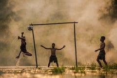 Οι ποδοσφαιριστές τα τρία παιδιά παίζουν το ποδόσφαιρο Στοκ φωτογραφίες με δικαίωμα ελεύθερης χρήσης