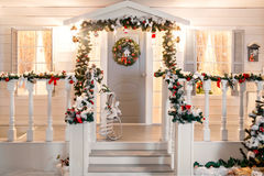 Οι πράσινες γιρλάντες του έλατου ή του πεύκου διακλαδίζονται με την κόκκινη και χρυσή πόρτα παιχνιδιών Χριστουγέννων στη βεράντα Στοκ Εικόνες