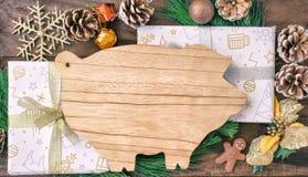 Οι προετοιμασίες Χριστουγέννων, τέμνων πίνακας υπό μορφή χοίρων, έλατο διακλαδίζονται, κώνοι και διακοσμήσεις Νέο έτος του χοίρου στοκ εικόνα