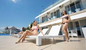 Οι προκλητικές γυναίκες χαλαρώνουν σε ένα ξενοδοχείο πολυτελείας κοντά σε μια θάλασσα Οι ελκυστικές νέες γυναίκες στα πολύχρωμα μ Στοκ φωτογραφία με δικαίωμα ελεύθερης χρήσης