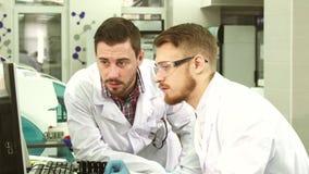 Οι προσεκτικοί εργαστηριακοί βοηθοί συζητούν τα αποτελέσματα των δοκιμών που βλέπουν στον υπολογιστή στοκ εικόνα