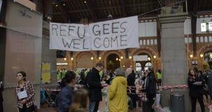 Οι πρόσφυγες εμβλημάτων καλωσορίζουν κρεμασμένος από τη φιλανθρωπία