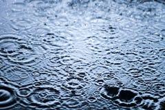 Οι πτώσεις βροχής στο νερό κλείνουν επάνω, υπόβαθρο Στοκ Φωτογραφίες