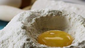 Οι πτώσεις λέκιθου στο αλεύρι σε σε αργή κίνηση, κλείνουν επάνω σκηνή Περιερχόμενος αυγά στο απόθεμα αλευριού Τρόφιμα μήκους σε π απόθεμα βίντεο
