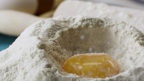 Οι πτώσεις λέκιθου στο αλεύρι σε σε αργή κίνηση, κλείνουν επάνω σκηνή Περιερχόμενος αυγά στο απόθεμα αλευριού Τρόφιμα μήκους σε π φιλμ μικρού μήκους