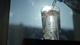 Οι πυροβολισμοί κινηματογραφήσεων σε πρώτο πλάνο του λαμπιρίζοντας νερού έχυσαν σε ένα γυαλί φιλμ μικρού μήκους