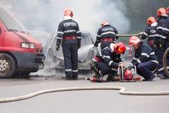 Οι πυροσβέστες εξαφανίζουν το αυτοκίνητο στην πυρκαγιά και άλλα δύο προετοιμάζουν τα εργαλεία απομάκρυνσης στοκ εικόνες