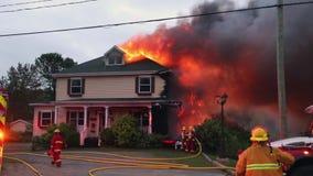 Οι πυροσβέστες μάχονται την καμμένος πυρκαγιά σπιτιών απόθεμα βίντεο