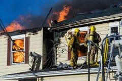 Οι πυροσβέστες μάχονται την καμμένος πυρκαγιά σπιτιών Στοκ φωτογραφία με δικαίωμα ελεύθερης χρήσης