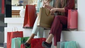 Οι πωλήσεις αγορών, θηλυκοί φίλοι που εξετάζουν τις αγορές στο μέρος συσκευάζουν κοντά στα πόδια στα μοντέρνα παπούτσια κατά τη δ απόθεμα βίντεο