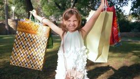 Οι πωλήσεις αγορών, χαρούμενο κορίτσι ανύψωσαν επάνω τις συσκευασίες με τις αγορές μετά από τα καταστήματα επίσκεψης φιλμ μικρού μήκους