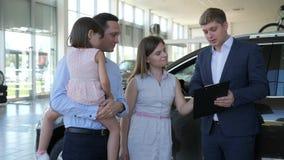 Οι πωλήσεις αυτοκινήτων, ελκυστικός διευθυντής πωλούν το αυτοκίνητο στους επισκέπτες, ευτυχής οικογένεια απόθεμα βίντεο