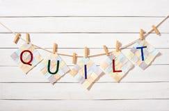Οι ραμμένες επιστολές, που συνδυάστηκαν ως πάπλωμα λέξης, σύνδεσαν με τα clothespins σε ένα σχοινί στοκ εικόνες